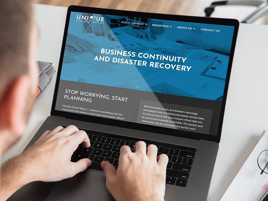 User Visiting Unique Computing Solutions Website on Laptop
